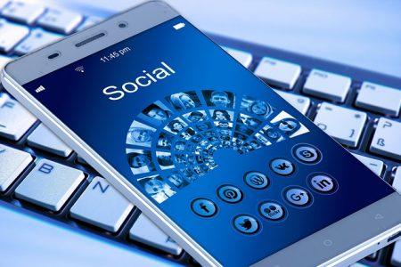 Jemand liest einen Artikel bei Facebook auf seinem Smartphone: Das Teilen fremden Contents in den sozialen Netzwerken hat viele Vorteile für Vertriebler.
