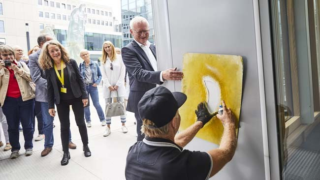 Der Künstler Thomas Baumgärtel markiert das Gebäude LVM-Kristall in Münster mit seiner Spraybanane. Unterstützung erhält er dabei vom LVM-Abteilungsleiter Immobilien Gerhard Laumann. (Bildnachweis: LVM Versicherung/Bernd Schwabedissen)