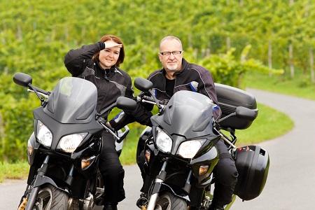 Zweiradfahrer mit Blick in die Kamera auf ihren Motorrädern
