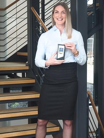 Kira Granz, Produktmanagerin Hausrat, freut sich über Platz 1 in der Sparte Hausrat und die Trophäe