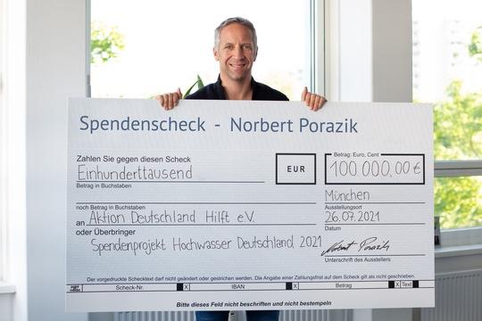 Norbert Porazik mit dem Spendenscheck an Aktion Hilft e. V.